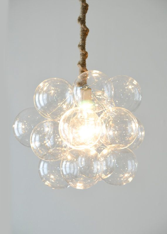 """Eighteen hand blown glass bubbles float around a center light globe, diffusing the light into a natural glow. The most compact of our custom chandeliers, Eighteen Bubbles is perfect for defining smaller spaces as a statement piece or even hanging over your bathtub (its fully grounded!). Product Specifications Bubbles 13"""" diameter x 13"""" tall Chandelier Height 48"""" (Bottom of Bubbles to Ceiling Canopy) *Can be customized to different lengths as needed. One 60w G30 Light bulb (included)…"""