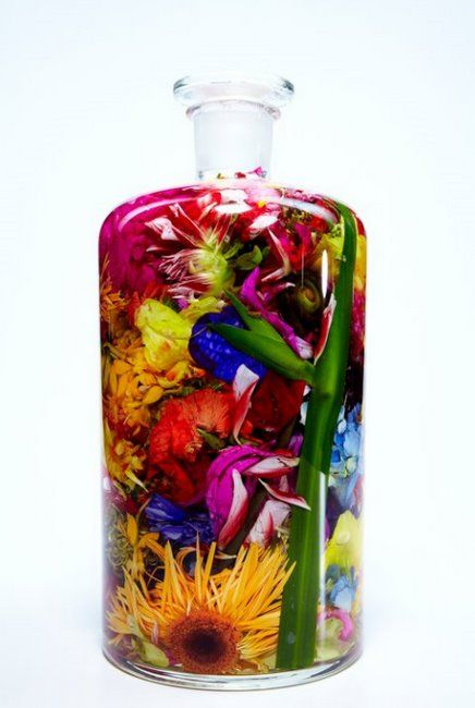 Glass bottle stuffed with brightly coloured artificial flowers, wow!!!