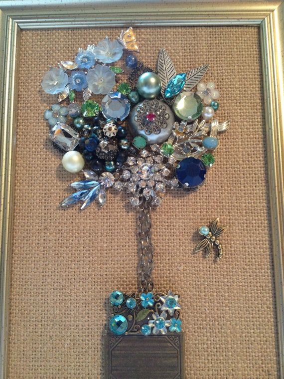 This silver tone 5x7 frame holds a collection of vintage and new costume jewelry arranged into a gorgeous floral topiary picture. The shades of blues
