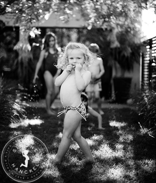 Poppy and the Sprinkler. We had to convince Poppy to go near the sprinkler, even though everyone else was thoroughly enjoying it! The hesitation on her face and her divine little tummy slay me every time. I love this photograph :) © Simone Hanckel Photography