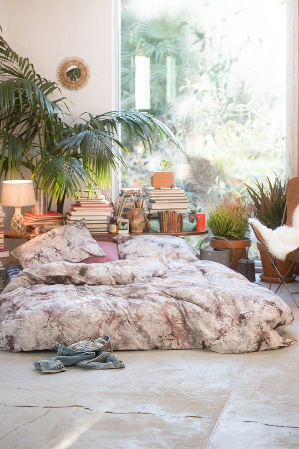 The Magical Thinking Acid Wash Duvet Cover is the star of this boho bedroom along with the mattress on the floor (who needs a bed) and the living plants.