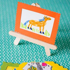 Miniature masterpieces deserve love, too. First, make a card stock hinge for the easel. Cut out a 1 1/2-inch-tall Y shape, with the three tabs of the Y the same width as a craft stick. Glue each tab to the end of a craft stick. For the easel's shelf, stack and glue together two sticks, then glue them to the front, as shown.