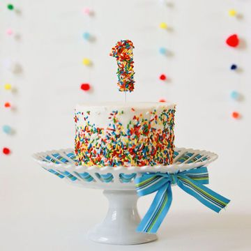 To make this 6-inch smash cake by Ashlee Marie, cover a white round cake with sprinkles, leaving the top plain. Use a number one-shaped cookie cutter on fondant, paint with clear vanilla, cover with sprinkles and let it dry overnight.