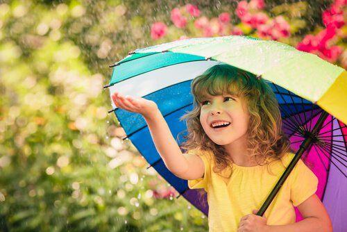 Niña feliz sonriendo con paraguas de colores