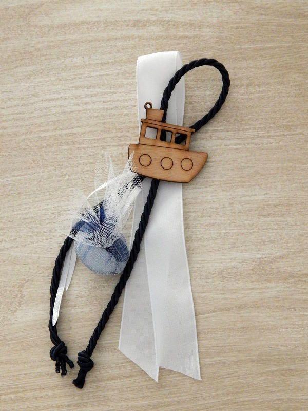 Κρεμαστή μπομπονιέρα βάπτισης με ξύλινο διακοσμητικό καραβάκι και σκούρο μπλε κορδόνι.
