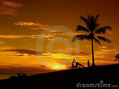 Stock Photo: Sunset Darwin, mother with baby, buggy, silhoutte, palm on beach