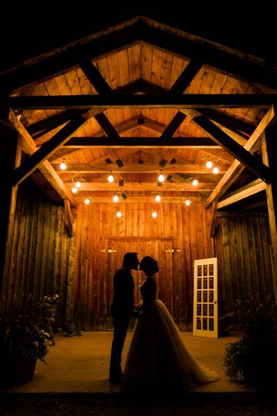 Les mariés se donner un baiser devant la grange au Vignoble de la Bauge, mariage rustique, robe de princesse
