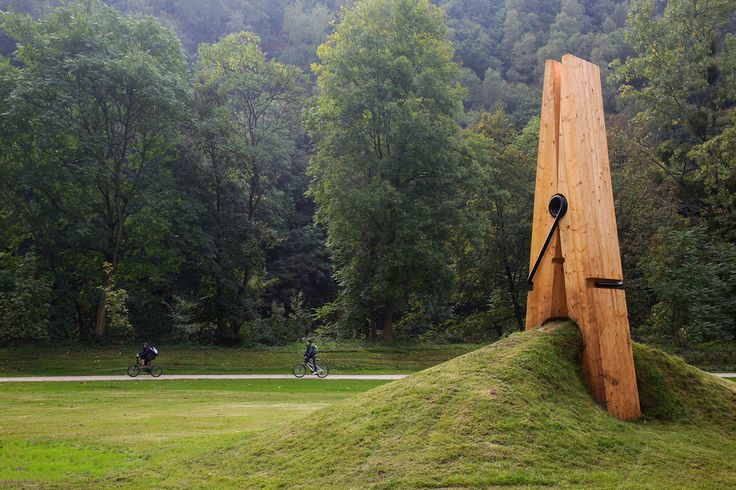 Land Art - GIANT CLOTHESPIN SCULPTURE by Uysal Mehmet Ali. Built for the Festival of the Five Seasons in Chaudfontaine Park, which lies on the outskirts of Liege, Belgium, a giant clothespin sculpture appears to be holding on to a mound of dirt and grass. Designed by Turkish artist Mehmet Ali Uysal, a professor of art at the Middle East Technical University, the giant sculpture is just one piece in a string of Uysal works that rely on flawless illusion.