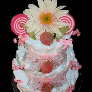 I still like diaper cakes with diapers aligned this way instead of rolled best. Use different size cake pans to position diapers then tie with ribbon.