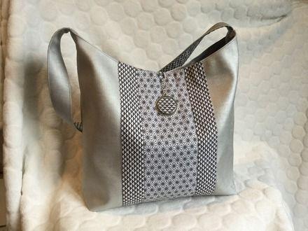 Sac à main en simili cuir gris perle. Sur le devant du sac deux bandes de tissu imprimés géométrique. Un medaillon est suspendu par une chaîne argenté. Á l'arrière du sa - 19900238