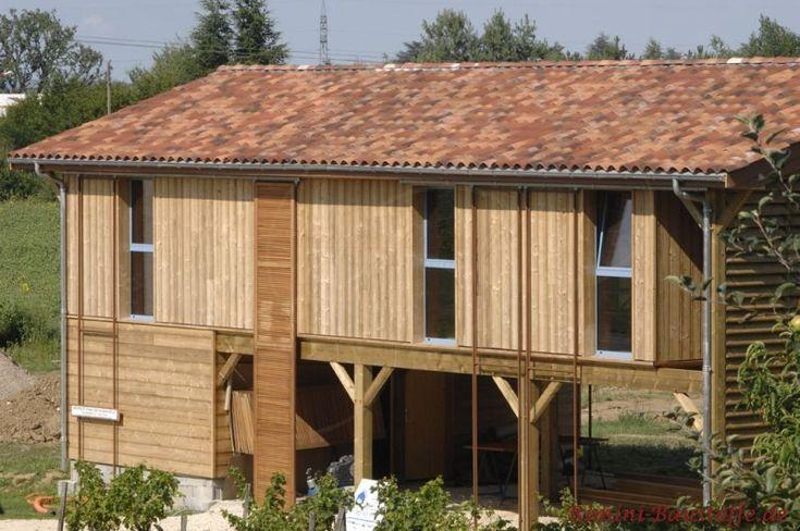 zweistöckiges Holzhaus mit bodentiefen Fenstern und einem sehr schönen Dach in einer Herbstlaubfarbe