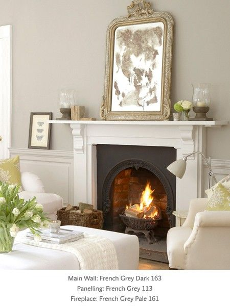 Love this fireplace!!  Living Room in neutrals, vintage mirror, beautiful fireplace, white upholstery, paint by Little Greene: colors French Grey shades.