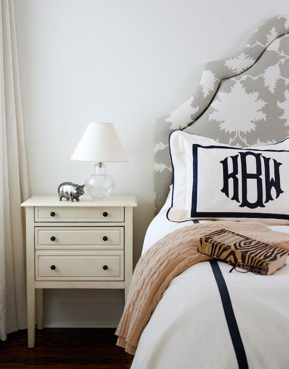 Elegant bedroom features light gray walls which frames an arched white and gray headboard upholstered in Mary McDonald Garden of Persia Dove Fabric on bed dressed in black and white bedding with monogrammed shams beside a three drawer cream nightstand topped with a small glass table lamp and silver piggy bank.