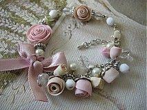 Náramok s ručne modelovanými ružami z polymérnej hmoty, priesvitnými a bielymi sklenenými brúsenými ohňovkami a voskovanými perlami. Ružičky sú v jemných odtieňoch staroružová a béžová. Doplnené textilnou mašličkou, ktorá je zafixovaná lepidlom. Retiazka a komponenty sú vo farbe platina. Zapínanie je na karabinku s predlžovacou retiazkou.