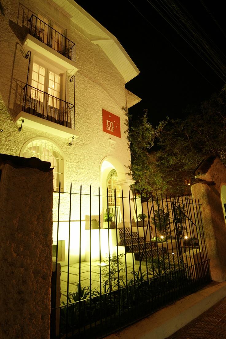Meridiano Sur Petit Hotel, acogedor alojamiento en hotel boutique. Grato y seguro hospedaje para su estadía en Santiago de Chile. Foto nocturna de la fachada.