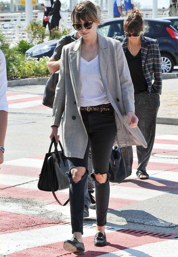 Look Dakota Johnson com sobretudo cinza calça rasgada.