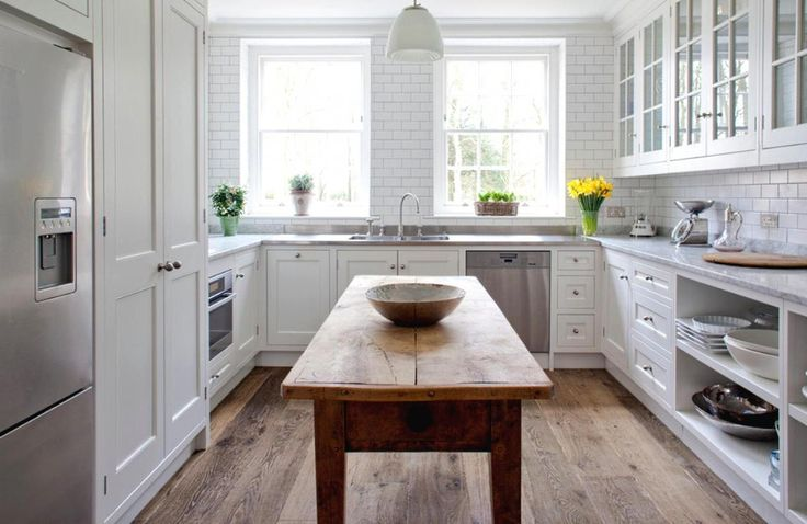 White U shaped kitchen with wonderful cabinets and storage also simply wooden table in the middle also windows with shades and lovely pendant