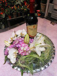 Vin flaske på rundt fat med blomster