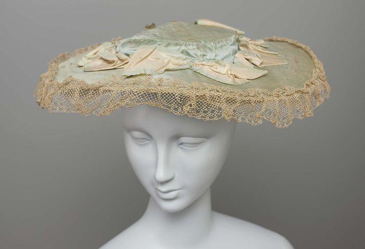 Flat straw hat covered with blue silk fabric, blue and white silk ribbon gathered around crown and tied in bow, white net trim around crown, white silk lining underneath. Late 18th to early 19th century. Overall: 1 x 15 in.