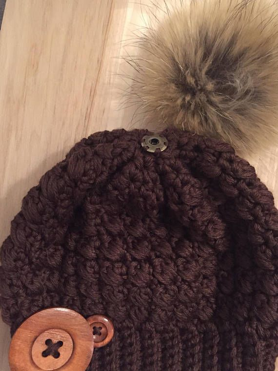 Tuque avec pompon de fourrure amovible super doux de 13-15 cm avec 1 gros bouton de bois de 60mm et 1 de 25mm 100% Superwash crochetée à 2 brins de laine . Très épaisse vu le motif Pour adulte , un beau brun marron soyeux pour celle-ci Femme: tour de tête de 55 à 60 cm,hauteur du bonnet