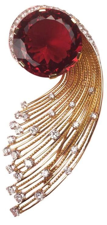 An important 18 carat gold spray brooch in the shape of a comet, the gold rays are set in platinum with 57 brilliant cut diamonds (circa 4 carat) in the heart a big slightly orange to purplish red tourmaline (elbaite or rubelite, circa 30 carats), signed and numbered: Sterle, Paris, 9006, circa 1950.