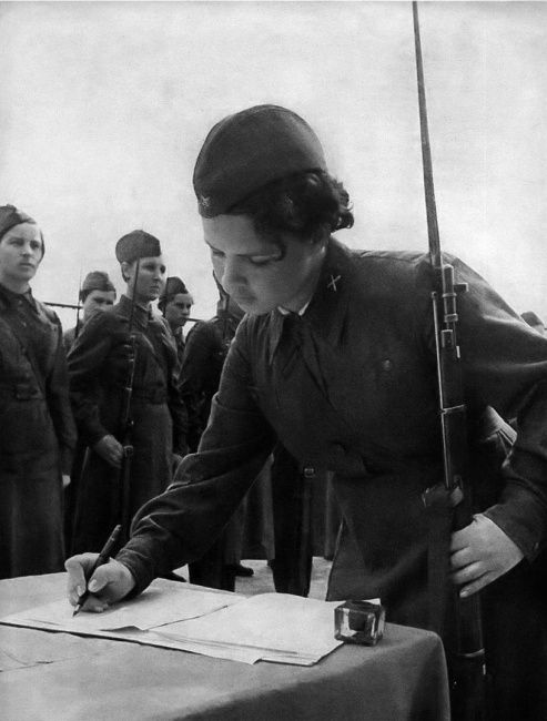 A female Soviet soldier of the Great Patriotic War signs the military oath while holding her rifle.