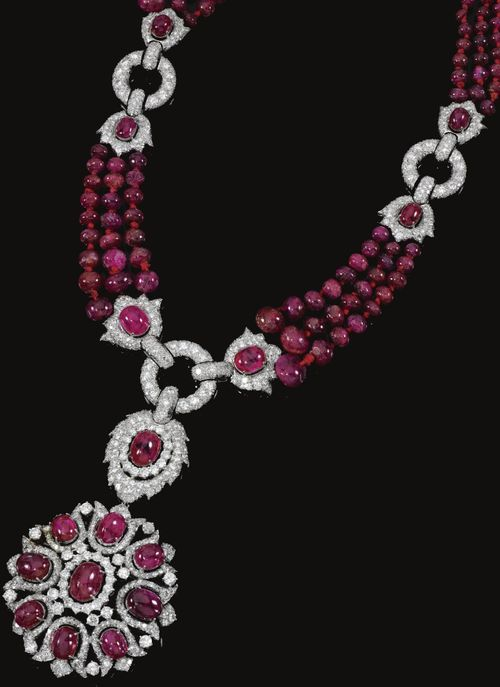 Ruby and diamond necklace/brooch combination, 1970s. Designed as graduated rows of polished ruby beads, suspending to the centre a pendant/brooch of open work floral design set with cabochon rubies and brilliant-, circular- and single-cut diamonds, to annular and foliate connecting links set with brilliant- and single-cut stones, mounted in white gold, length approximately 533mm, pendant is detachable and may be worn as a brooch. Sotheby's.