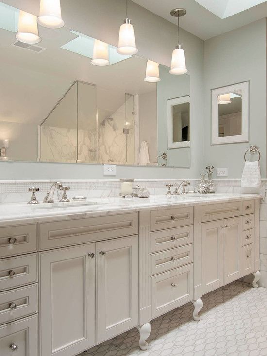 Beautiful traditional bathroom with white cabriole footed double vanity and gray green wall color. The traditional vanity pairs with crystal hardware, marble countertops and a mini marble mosaic backsplash. A large frameless mirror hangs on the wall above the vanity with three frosted glass ceiling mount pendants hanging over the sinks. A small recessed mirror fronted medicine cabinet hangs over the the far end of the vanity. The floors are tiled with a marble mosaic floor tile.