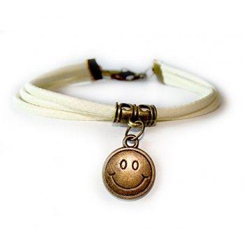 """Bransoletka """"z uśmiechem do świata"""". Bransoletka z woskowanego sznurka w kolorze waniliowym, z uśmiechniętą zawieszką w kolorze miedzianym."""