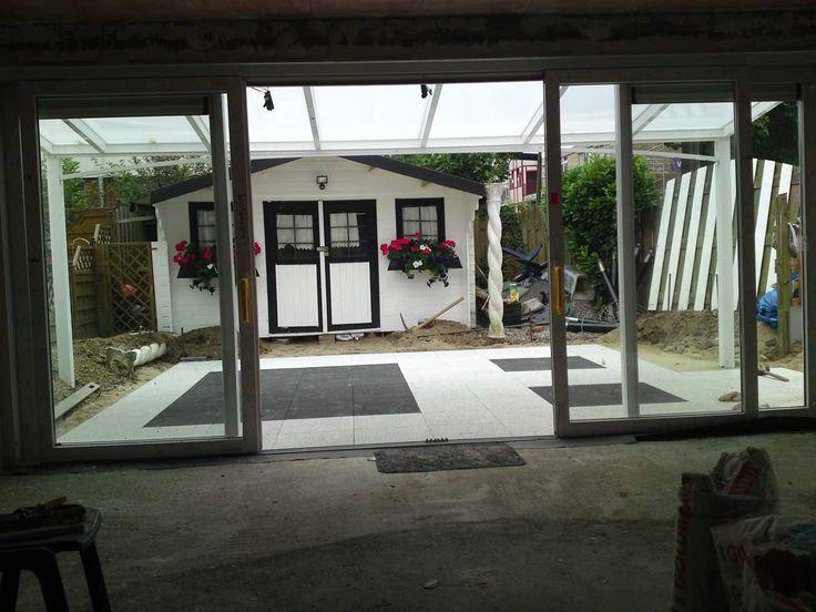 Overdekt terras met sierbestrating van kleurechte betontegels.