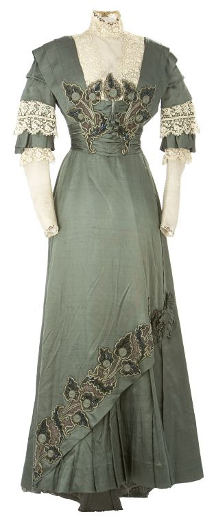 Woman's Dress, 1910, custom made, Eaton's Department store, Toronto, Canada. The skirt, which is longer in the back than the front, fits smoothly over the hips, but has an asymmetrical overskirt slanting from the hem to the knee at the side seam. The bodice is accented with a high lace collar, and a beaded and embroidered passementerie appliquéd above the waist.
