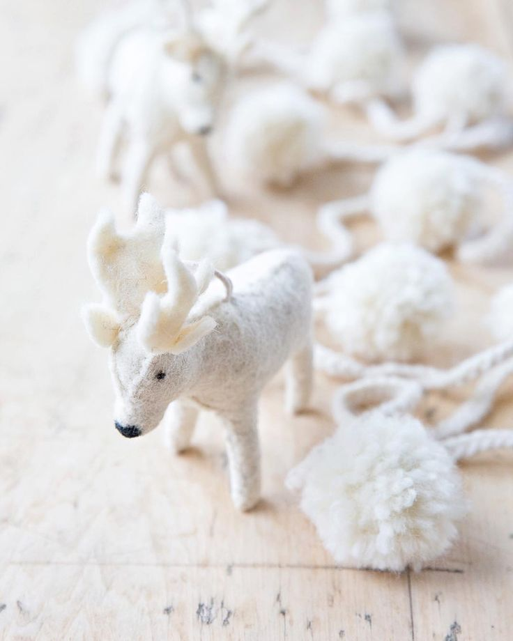 Sweet white felted wool moose and pom poms upon a rustic farm table - A Rosy Note. #christmasdecor #whitechristmas #farmhousechristmas #feltedwool #whitechristmas #frenchfarmhouse