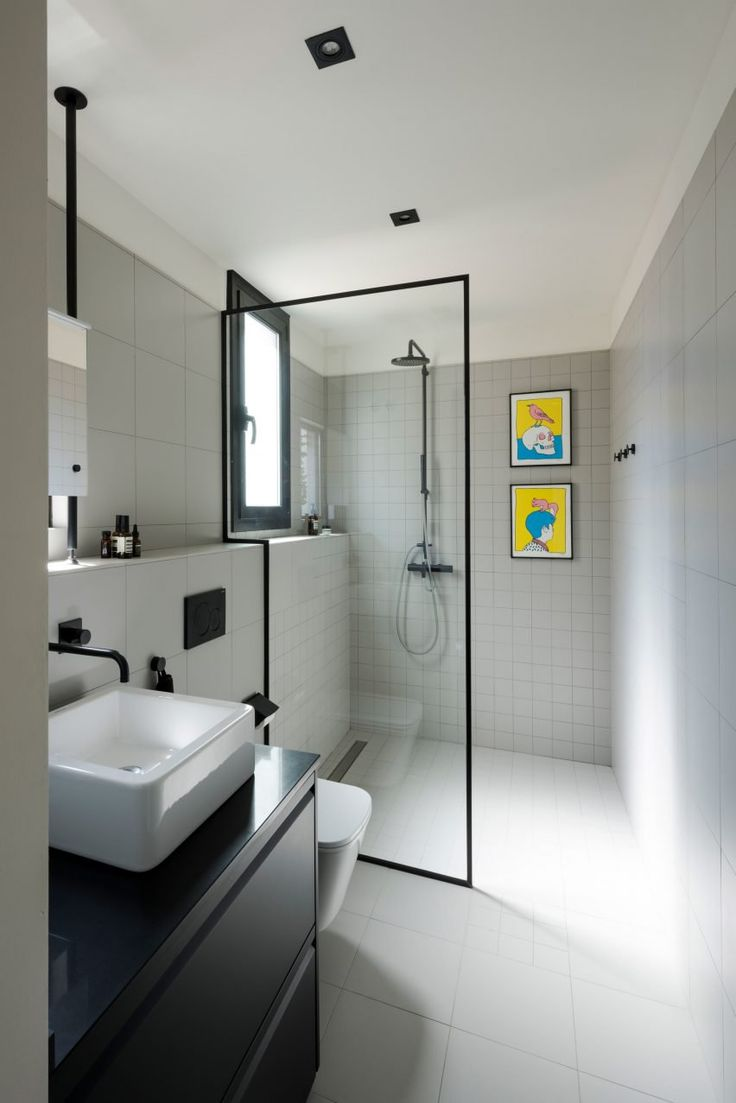 Varying sizes of tiles make up the wall and floor surfaces of the bathroom, which echoes the colour scheme of the kitchen, with black cabinets and matching faucets and detailing. The shower screen is formed from a singular piece of glazing, framed with a black steel rim.