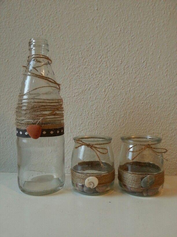 Bottiglia e vasetti in vetro con corde e sassi