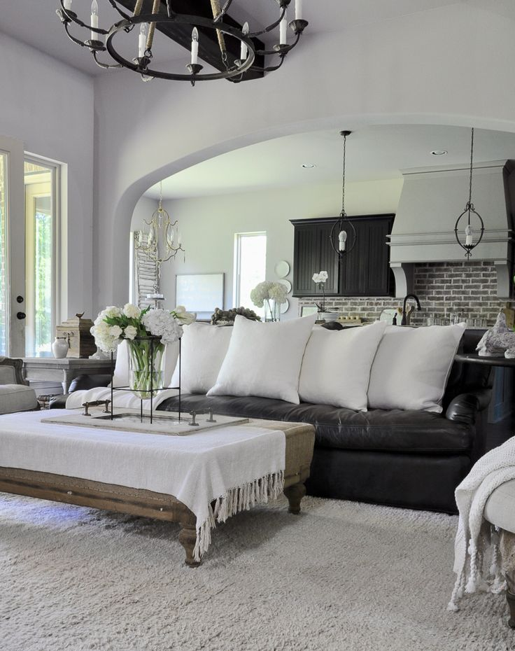 Neutral Living Room with Leather Sofa with Large White Pillows by Decor Gold Designs. I could do a leather sofa that way. It keeps it light.
