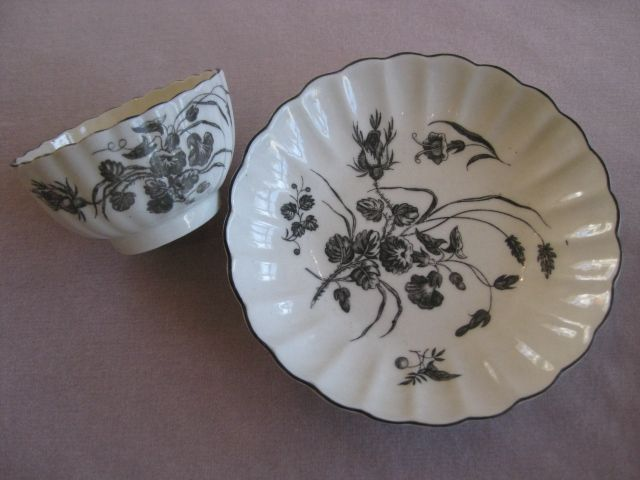 A very rare Worester  fluted tea bowl and saucer finely printed in black  with flowers and leaves including convolvulus , rose bud and others. Black line to the edges. Unmarked   Circa 1770 See V & A Schreiber Collection