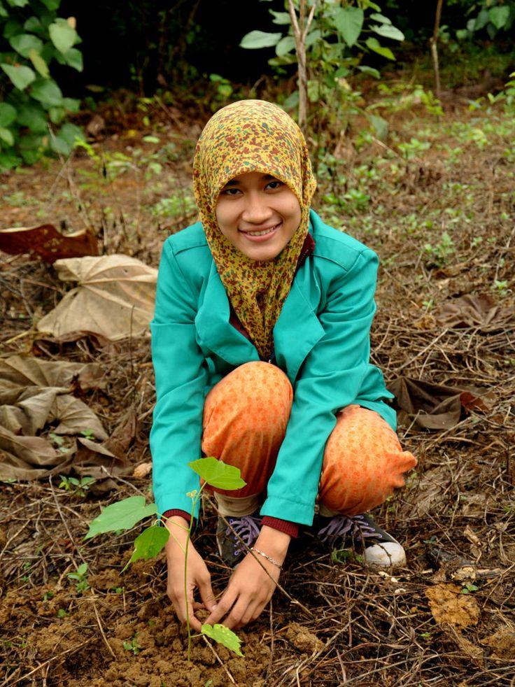 student planting tree for Orangutan habitat restoration