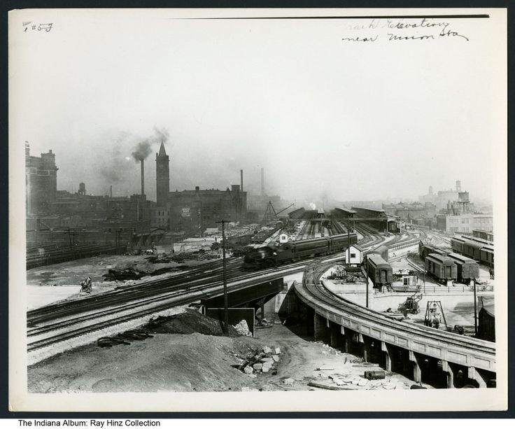 Photo of a railroad yard near Union Station, Indianapolis, Indiana, ca.1915 - Photo showing a passenger train speeding through a railroad yard. Union Station and Spencer House are seen in the background.