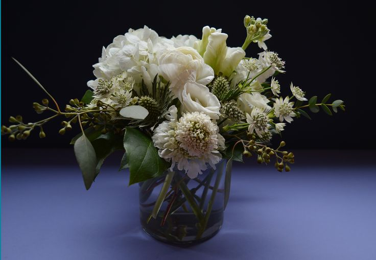 all white table arrangement for a Brooklyn wedding featuring hydrangea, lisianthus, scabiosa, eucalyptus, parrot tulips and ranunculus.