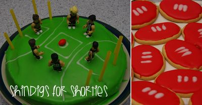 AFL footy oval (round) cake with Coles AFL minifigure players and ball, straws for goal post and white piped icing for ground markings. Red iced arrowroot biscuits for footballs with white icing piped laces.