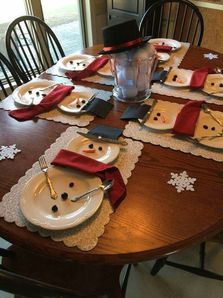 Snowmen place settings! Red cloths napkins, black disposable napkins, olives for buttons and eyes, carrot nose, silverware for arms and part of the hat.