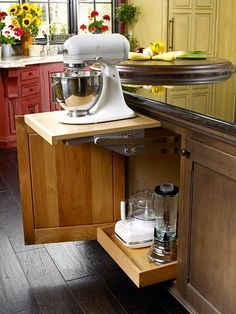 Keep counters clear and the look of your kitchen flawless by stashing small appliances away. Here a spring-loaded shelf in an island cabinet easily moves the mixer to countertop height. An outlet inside the cabinet eliminates messing with the cord. A deep pullout drawer below corrals other small appliances into one central location.