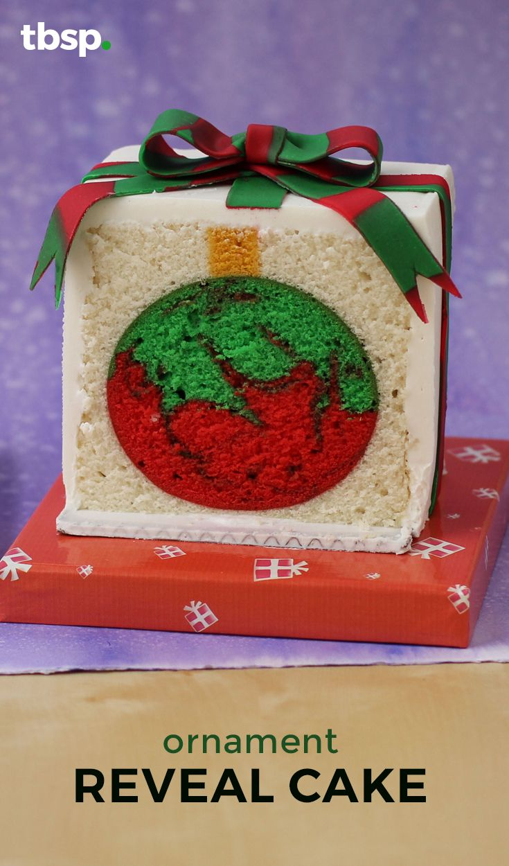 A cake decorated to look like a Christmas present is cut to reveal an ornament hiding inside.