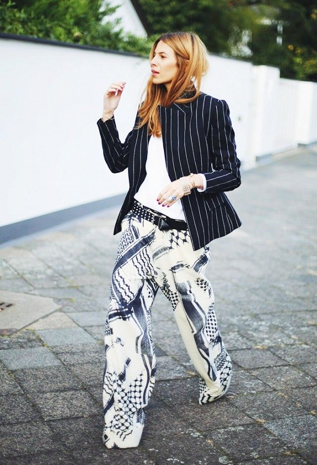 Maja Wyh wearing a pinstripe jacket with printed wide-leg trousers and a belt.