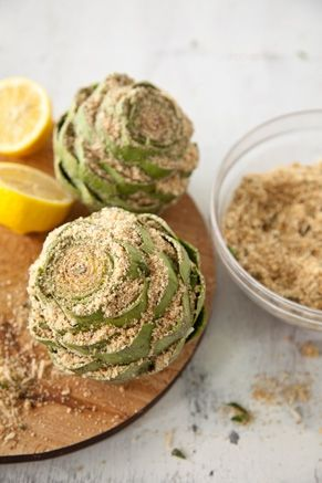 Stuffed Artichokes 4 cups plain breadcrumbs 1 cup grated Parmesan/Romano cheese blend 1/2 cup extra-virgin olive oil 3 tablespoons chopped fresh flat-leaf parsley 5 cloves garlic, minced 2 lemons, plus 4 lemon slices 1/2 teaspoon salt 1/4 teaspoon freshly ground pepper 4 large artichokes