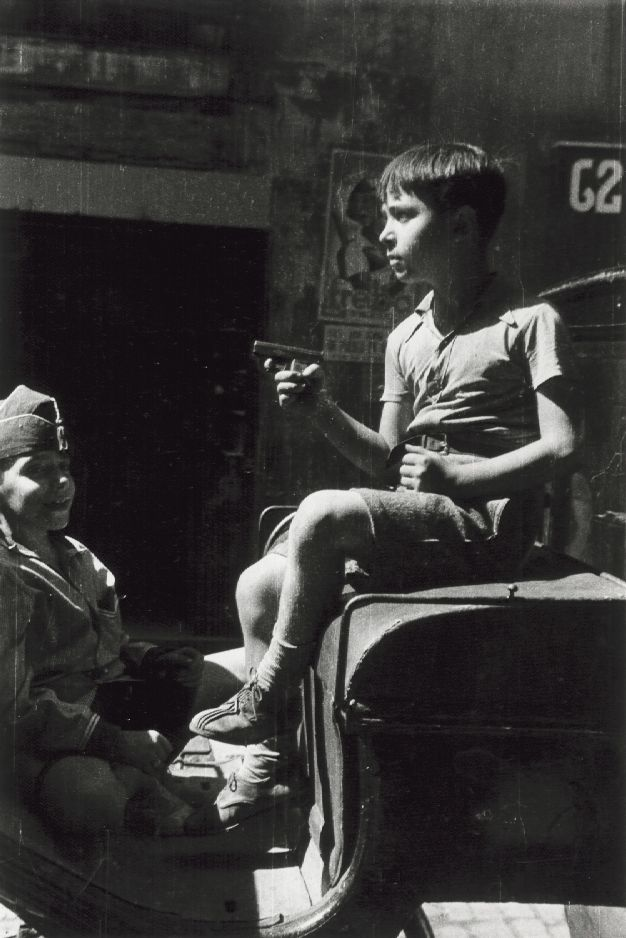 Robert Capa. Young Boy Holding Toy Pistol, Spain, 1930's    http://semioticapocalypse.tumblr.com