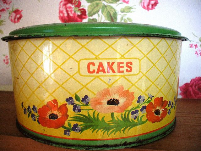 A wonderful vintage green and yellow cake carrier with a red poppy floral design...
