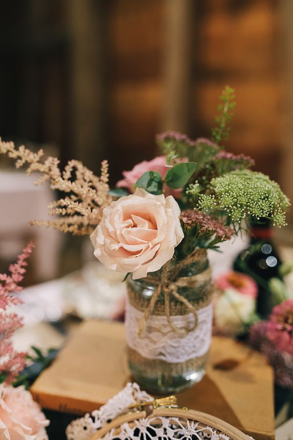 Pretty pink rose in a jam jar with lace, from 'A 1920s and 1930s Antique and Old Fashioned Vintage Inspired Barn Wedding'.  Photography http://www.brighton-photo.com/