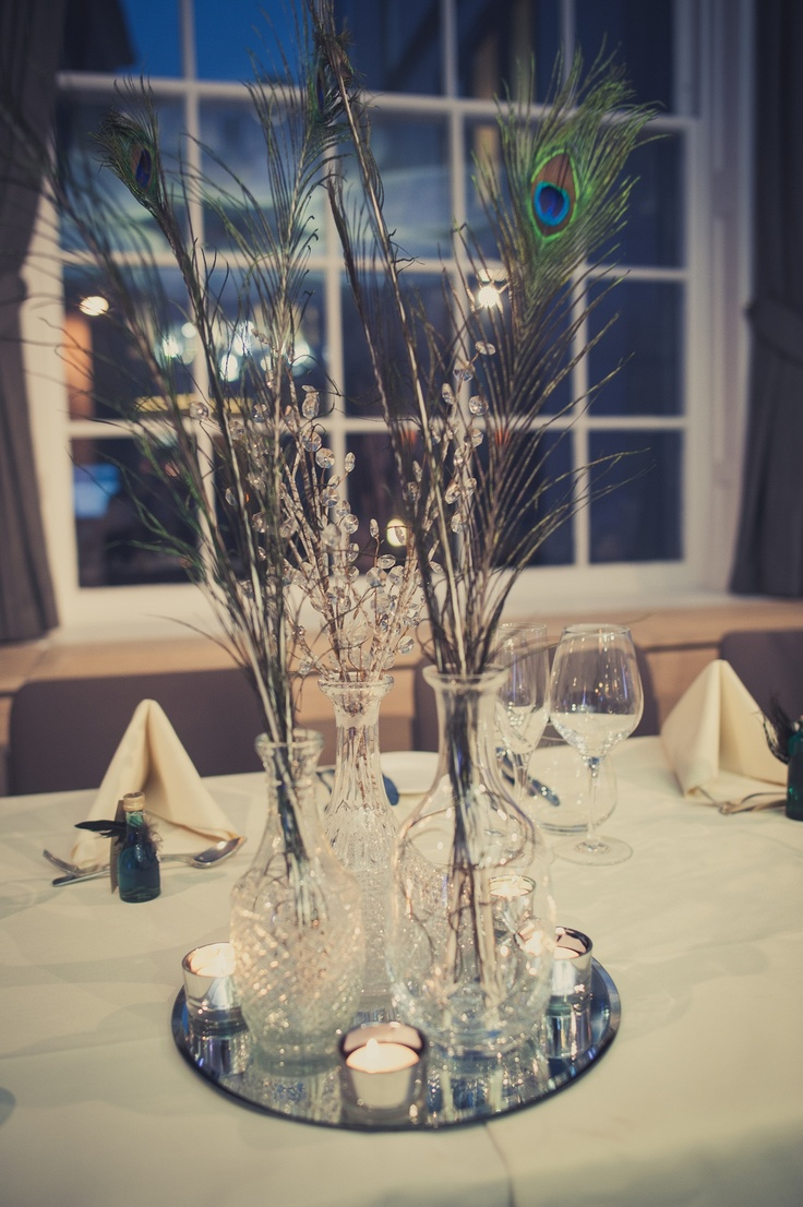 Peacock feathers in antique vases and decanters as the centerpieces RSA House London Wedding