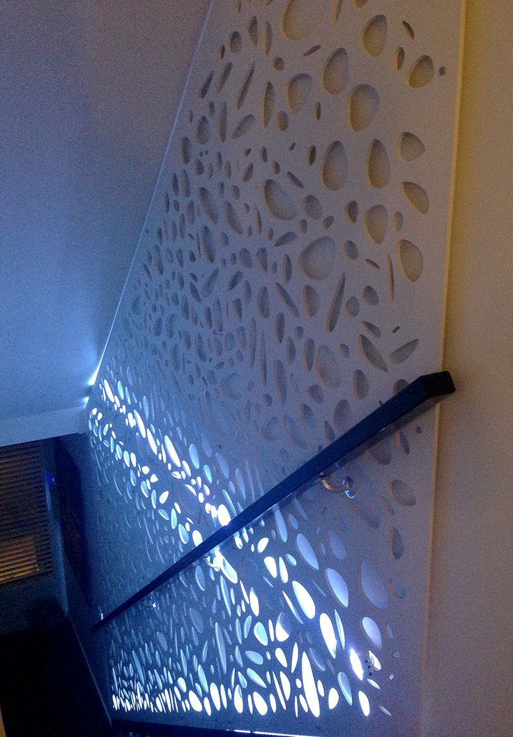 Laser cut decorative screen installed in a modern stairwell. This is QAQ's 'Cayman' design in 6mm MDF, painted white, hung with standoffs.  LED lights are installed behind it.
